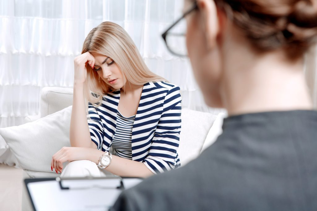 Young blond woman sitting on a couch holding her head sadly crossed telling about her problems, doctor with clipboard listening to them and making notes during therapy session, selective focus